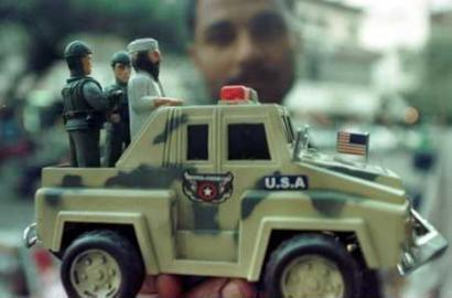 A Pakistani shopkeeper displays a limited edition toy truck depicting Osama bin Laden commandeering a US military vehicle.  Many people in the region see bin Laden as all powerful and believe he will one day govern the United States if he is not hit first by a missile aimed at innocent civilians. (Reuters)