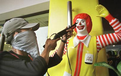 An Indonesian Muslim protester points his gun at Ronald McDonald during an anti-war demonstration at a McDonald's restaurant in Jakarta.  The protester maintained the threatening position for several minutes, became agitated at Ronald's apparent comical indifference, then realized the figure was not real.  The standoff ended without injury, but the manager had the assailant arrested.  (Reuters)