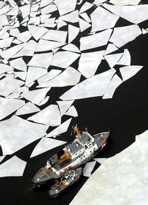 Coast Guard cutters work their way up the Kennebec River near Richmond, Maine, on a contract from philanthropist Ted Turner.  The millionnaire is trying to get into the much-sought after Guinness Book of World Records for assembling the largest ice jigsaw puzzle ever.