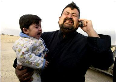 An Iraqi man and his son express dismay upon hearing of the cancellation of the Bon Jovi concert originally scheduled for April 21 in the Baghdad Civic Center, for which he and his family had five tickets.  The band has been the backbone of rock radio stations in Iraq since the mid-80's, and Bon Jovi bumper stickers can be seen on all but the blown up cars in Iraq.  (Associated Press)
