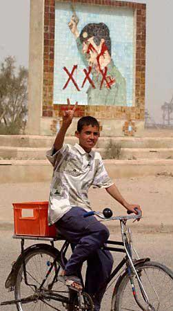 A young Iraqi street gang member pedals away while flashing the peace sign after defacing a mural of Saddam Hussein in the city of Umm Qasr.  The boy is a member of the Triple X Gang, which is pushing for Vin Diesel as the replacement for the troubled dictator.  (Associated Press)