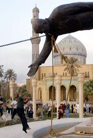 An Iraqi citizen is seen jumping to eagerly high-five a huge statue of Saddam Hussein.  The man obviously had watched too many Saturday morning cartoons and smoked a little too much of the wacky weed.