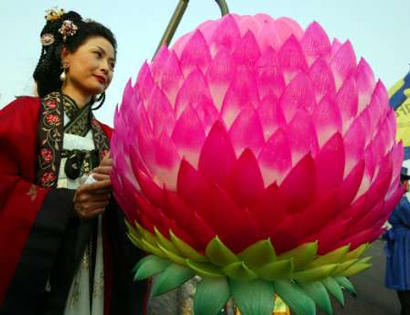 Contestants stand beside their entries in the 103rd Annual Lotus Growers Competition in Seoul, South Korea.  This woman placed 3rd in the field of 342 with the winner's lotus bearing a slight resemblance to Louis Anderson, a major celebrity in South Korea.