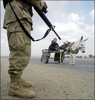 Iraqi men ride a donkey-pulled cart past a US soldier providing security for a US military armored vehicle convoy temporarily parked on the side of a road near Baquba.  The donkey, which did not react to English commands from the soldier to halt, was shot and killed shortly after this photo was taken.  The Iraqi men were allowed to turn back on foot.  (Associated Press)