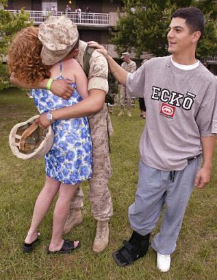 Marine Lance Cpl. Robert Torres, center, from Decatur, Texas, embraces his friend?s wife Denarae, left, as he gets a pat on the back from her husband Cpl. Carlos Paredes, right, Saturday, May 17, 2003, at Camp Lejeune, N.C., after Torres and other members of the 2nd Force Service Support Group returned from deployment.  Torres, unmarried, was allowed to hug Paredes? wife as part of a friendly gesture between the two soldiers.  ?He doesn?t have a woman in his life right now,? Paredes said, ?So I thought he could use one of those classic ?returning from war? embraces.?  (Associated Press)