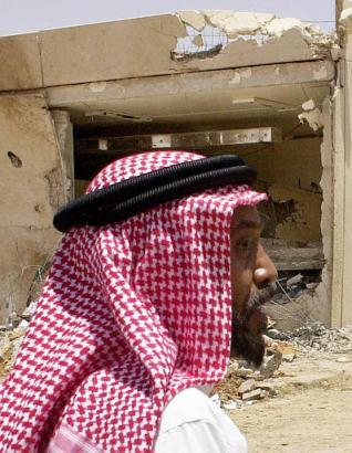 Security manager Mohamed al-Ahmed, on Saturday, May 17, 2003, looks at the bomb damage at Jadawel compound, one of the three compounds that was attacked in recent coordinated terrorist strikes in Riyadh, Saudi Arabia. Ironically, the security manager was wearing a dish towel he had taken from a nearby Denny?s.  (Reuters)