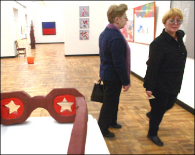Visitors to a museum in Frankfurt Germany stride by the Elton John Exhibit.  Germans have long been known for their varied tastes in music and art, such as the red and blue thing in the background and the orange mop bucket exhibit.