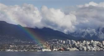 A rainbow stretches across Vancouver Harbor in Vancouver, British Columbia, recently.  Since Vancouver does not have naturally occuring rainbows, one had to be trucked in from an undisclosed location.  Tragically, however, an Olympic athlete was crushed to death when struck by the pot of gold that accompanied the atmospheric phenomenon.  (Associated Press)