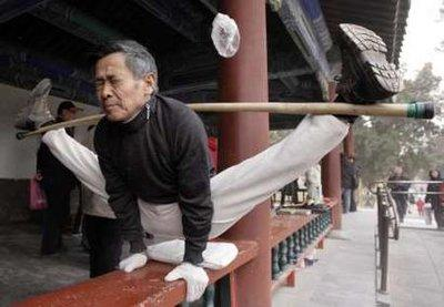 A local man prepares himself for nutsack surgery during a morning exercise session at the Temple of Heaven park in Beijing.  Ling Chow Chi, 54, will have his nutsack surgicalized for an unknown reason due to undisclosed symptoms.  The position he is practicing is one he will be required to maintain throughout the entire surgerilaztionification.  (REUTERS)