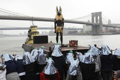 Brooklyn, NY (AP) - The Egyptian god Anubis visited followers under a picturesque Brooklyn Bridge, on Tuesday, March 23, 2010.  New York was Anubis' fifth stop on his American tour, designed to feel out support for a possible 2012 presidential run.  Political watchers are already criticizing his 'Give-up-your-first-born' tax proposal and Vice Presidential selection of Nancy Pelosi, as political suicide.