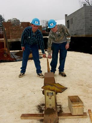 Habitat for Humanity volunteers Michael Walker, left, and Steven Petersen prepare to remove a newly made brick from a press in Americus, Ga., Dec. 10, 2002. They are helping to build Habitat's new Global Village & Discovery Center in Americus, which will highlight the group's international homebuilding work. By making the bricks one at a time this way, the group expects to complete the center by 2078. (Associated Press)