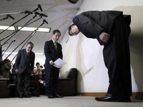 Japanese government officials pause to examine and appreciate carpeting prior to beginning a news conference in Tokyo recently.  The island nation contains no textile mills of any sort and, as a result, must import all of its carpeting and rugs which leads to an almost child-like fascination with quality floor coverings. (REUTERS)