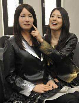 A model (R) touches the face of a humanoid robot called 'Geminoid-F' (L) at a press conference in Osaka. Japanese researchers said Saturday they have developed a humanoid robot that can laugh and smile as it mimics a person's facial expressions.  