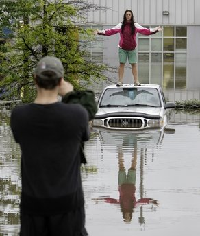 A homeless man in Nashville, TN, stands atop a submerged SUV Sunday, May 2, and preaches to the gathered masses.  The sermon, planned last week, did not have the turnout expected but the man vowed to appeal to God to 'dry the waters and save the believers' if onlookers took pictures and posted them to the internet.