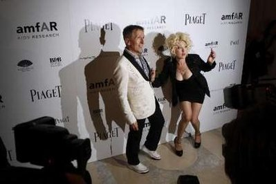 Singer Cyndi Lauper arrives with Simon Doonan to attend the amfAR (The American Foundation for AIDS Research) Inspiration Gala in New York June 3, 2010.  During most of the photo opportunity, Lauper had to urinate and made no secret about it, exclaiming multiple times, 'Pee's coming down my leg!  I can feel it!'
