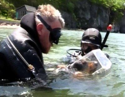 Divers recover the head of a dog frozen in a block of ice and found floating in a river near Charleston, West Virginia.  'Every year, we get the same things from these kids around here,' Sheriff Richard Buncombe stated, 'always freezing parts of animals and setting it afloat just to get a rise out of people.'  Buncombe says the prank has been going on since the early 1980's.  (Associated Press)