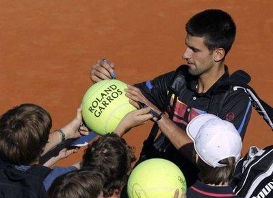 Serbia's Novak Djokovic signs giant tennis balls that will be used in the inaugural match of the Blind Tennis Players League (BTPL) which begins next month in Morocco. Djokovic, whose cousin is a blind tennis player, provided funding and other support for the league which will be the first to use the massive, easy-to-hit balls. (REUTERS)