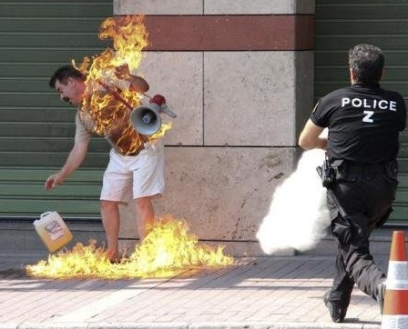 A member of Atlanta's new 'Police Z' tactical division arrives to extinguish a man who had just set himself on fire on a downtown sidewalk. Self immolation has been on the rise among fans of professional sports in the southern city in recent years, as the Braves, Falcons, and Hawks leave little to cheer about. The new police division is a first in the US and patrols primarily around the stadiums where the teams play, as over one hundred such acts were reported in 2011. 'If coaches and ownership can't light a fire, maybe we can,' stated Jerry Cincella, 43, who ultimately survived this incident. (Associated Press)