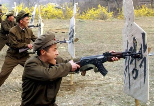 Members of the Worker-Peasant Red Guards of North Korea attack a South Korean display of cardboard dummies along the DMZ during a skirmish on April 27, 2012. Two North Koreans were reported injured when they tried to eat the rice paper covering the displays and bit into staples.
