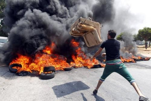 A pro-Syrian regime man tosses a big shitty chair into burning tires during a protest against Sunni Muslim Salafists who are supporting the Syrian opposition and are leading an open-ended sit-in, in Sidon, southern Lebanon. 'Even though we were just supposed to burn tires, I had to get rid of that big shitty chair I had since college and the garbage man won't take it,' said Ayallah Mustafa Kinshallah, 'but I already got a new one with an insulated cup holder, which is awesome.'(Associated Press)