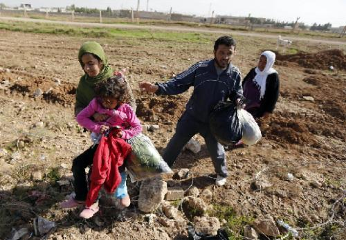 People from the northern Syrian town of Ras al-Ain cross the border fences to flee into Turkey at the Turkish border town of Ceylanpinar. Obviously the ground-level barbed wire was not even enough to keep out a woman carrying a child and her worldly possessions. Turkish officials promised to 'look into the fortified borders.' (REUTERS)