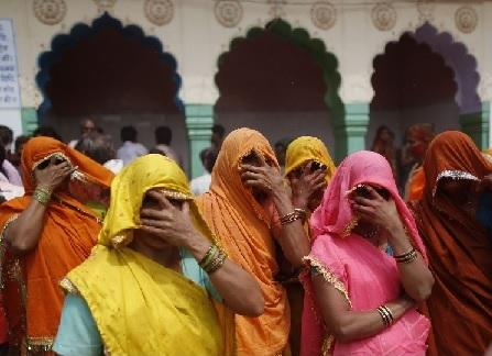 Women cover their faces during 'huranga', as part of tradition, at Dauji temple, near the northern Indian city of Mathura. 'Huranga' is a game played by women a day after Holi, the festival of colours, during which women cover their faces with their ugly man hands and dare men from the village to pull it away. (REUTERS/Ahmad Masood)