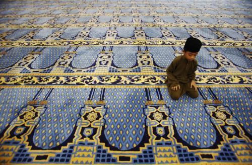 A Muslim boy performs a prayer at a mosque in Pekan, in Malaysia's central state of Pahang, on the world's biggest shittiest carpet. 'It's ugly as hell,' said Shaktar al Ghassin, a local official who asked to remain anonymous. (REUTERS)