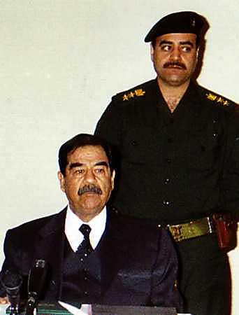 Saddam Hussein holds a press conference to discuss and display the inherent difficulties the United States would have in trying to assassinate him in the event it may one day occupy Iraq. 'We all look alike, you see,' Hussein said Friday. 'A little beret, maybe a different suit, and the Americans won't know which is me,' he added.