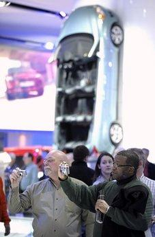Paul Sachar, left, 58, of Erie, Pa., and Gary Powell, 42, of Toledo, Ohio, take photos of the 2012 Ford Focus ST with the All-New Ford C-MAX hanging on the wall in the background, during the opening day of the North American International Auto Show in Detroit. The vehicle will be the first to employ Ford's new Vertical Parking Technology (VPT), which will allow the car to indefinitely adhere to any vertical flat surface while parked. (Associated Press)