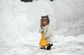 Ilona Chisholm, 13 months, helps her mom shovel snow out of their driveway using a rake in Cohassett, Massachusetts.  'Children are small and stupid,' said noted child psychologist Dr. Douglas Hopper, 'and they are often ill-equipped to determine the proper tool for any particular job because they are just pretty much dumb.'  Hopper added that any kind of plastic shovel would have been 'far superior to a freaking rake--rakes are for dirt.'  (Associated Press)